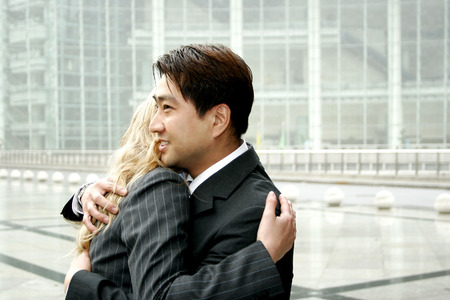 A man and a woman in business suits hugging  photo