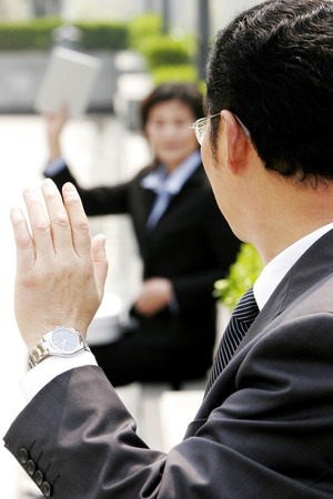 bespectacled man: A bespectacled man waving to a woman