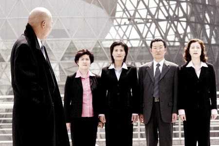 A bald man watching a group of business people standing in a row photo