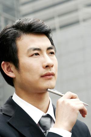 traje sastre: El hombre en traje de negocios que sostiene una pluma