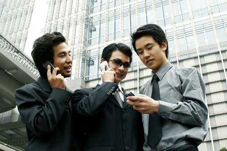 desirous: Three businessmen using hand phones