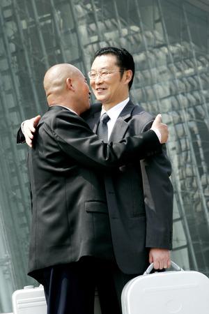bespectacled man: A bald man hugging a bespectacled man  Stock Photo