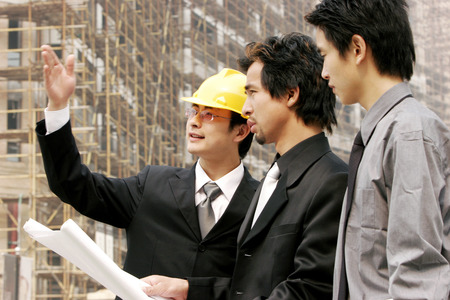 Two men and an architect at the construction site  photo