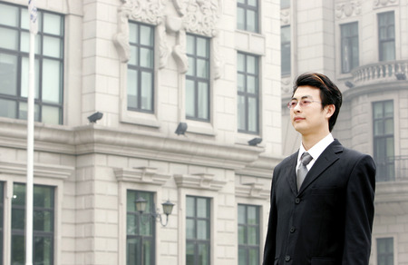 desirous: A bespectacled man in business suit standing in front of a building