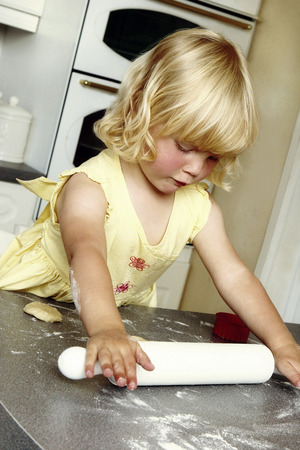 figuring: Girl playing with a wooden rolling pin