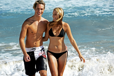 infatuation: A couple taking a stroll on the beach Stock Photo