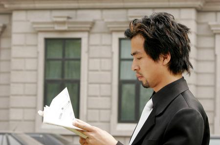 aspirant: Side shot of a businessman reading a newspaper