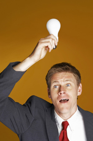 desirous: Businessman holding a light bulb on top of his head  Stock Photo