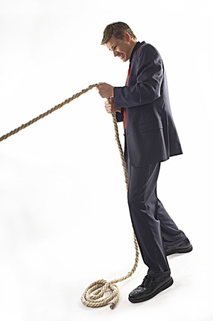 Man in business suit pulling a rope with all his might  Imagens