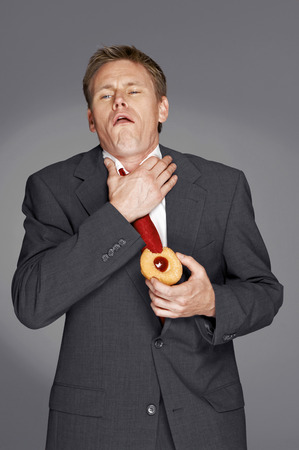 Man in business suit choked on a tart  Stock Photo