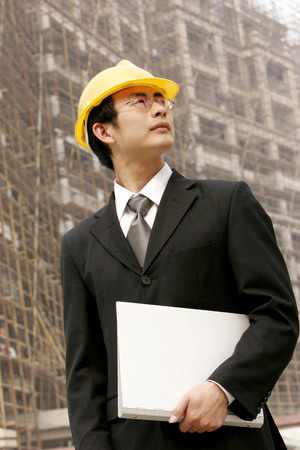 aspirant: Architect holding a document at a construction site