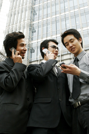 aspirant: Two men talking on the hand phone while the other one text messaging