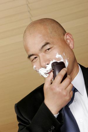 aspirant: Bald man in business suit shaving his moustache  Stock Photo