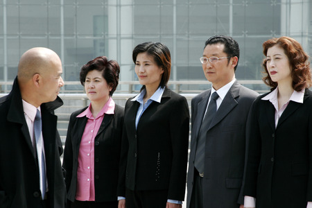 check ups: A bald man watching his employees standing at attention
