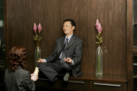 Woman worshipping a businessman who is sitting on the shelf meditating  photo