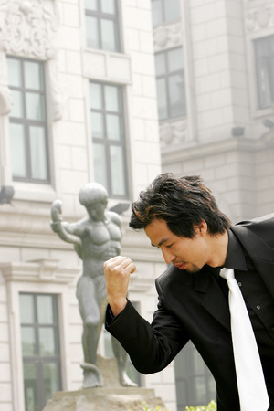 desirous: Man in business suit imitating a statues pose