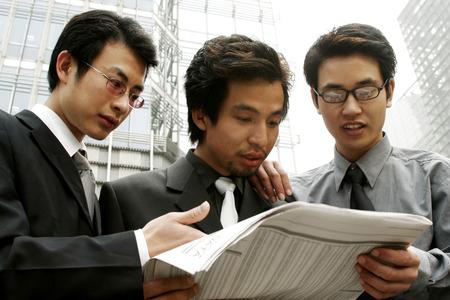aspirant: Three businessmen sharing a newspaper