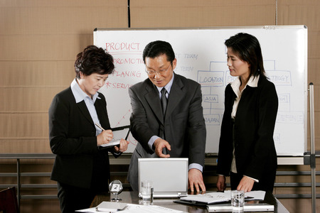 Manager showing some information on his laptop to his assistants  photo