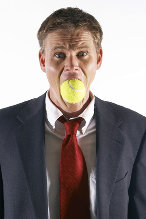 Businessmans mouth being stuffed with a tennis ball