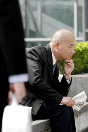 aspirant: Bald businessman sitting on the bench reading newspaper
