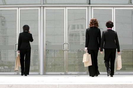 aspirant: Back shot of three business women walking into a building