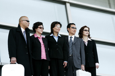 desirous: Business men and women in sunglasses standing in a row  Stock Photo