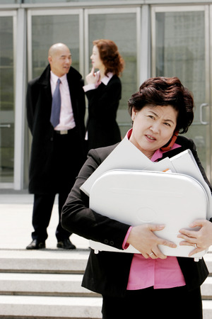 Business woman talking on the hand phone while carrying a briefcase of documents  photo