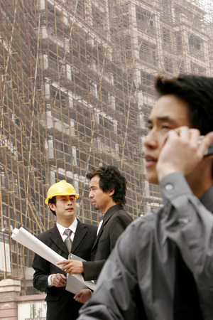 Man talking on the hand phone while his colleague talking to the architect  photo