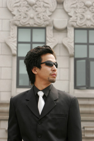 aspirant: Businessman with sunglass standing in front of a building