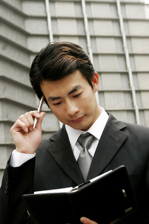 aspirant: Businessman thinking of things to write on his organizer