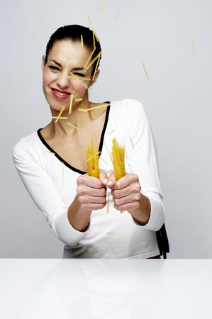 Woman breaking dry spaghetti Stock Photo