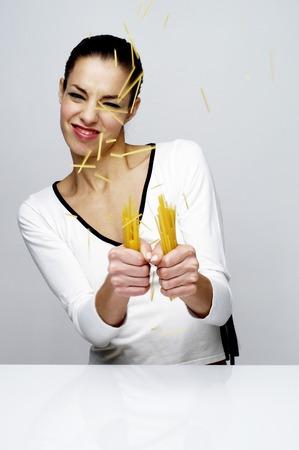 flavoursome: Woman breaking dry spaghetti Stock Photo