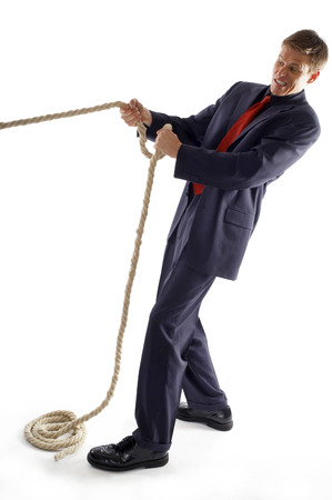 desirous: Man in business suit pulling a rope with all his might  Stock Photo