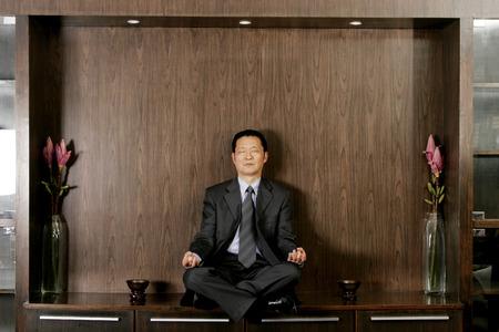 traje sastre: Hombre en traje de negocios sentado meditando en el estante Foto de archivo