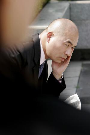 aspirant: Sad looking bald man sitting on the bench  Stock Photo