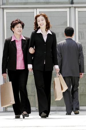 aspirant: Two business women carrying paper bags