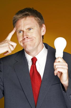 aspirant: Businessman thinking while holding a light bulb