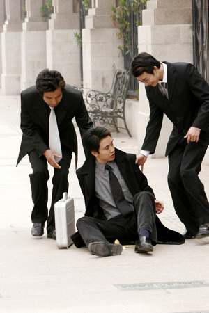 Two men helping his friend up after he slipped