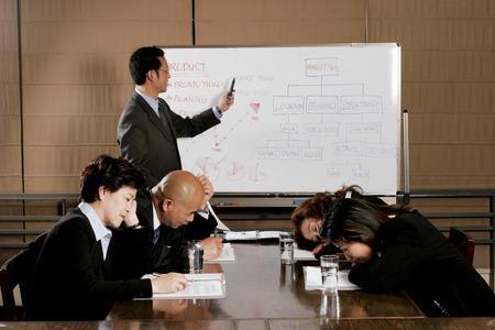 男性と女性のマネージャーによって退屈なプレゼンテーションを聞いた後眠りに落ちる