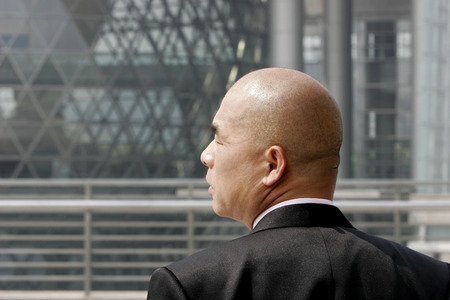 desirous: Back shot of a bald man in business suit looking to the side  Stock Photo