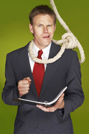 Businessman feeling uncomfortable with a rope hanging around his neck  photo