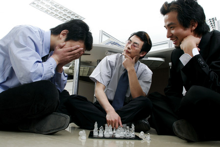 Three men playing chess in the office  photo