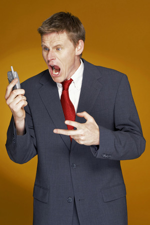 aspirant: Man in business suit shouting angrily on the hand phone
