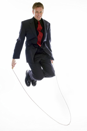 desirous: Man in business suit playing with skipping rope