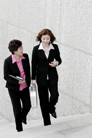 Two business women chatting while walking up the stairs  Stock Photo