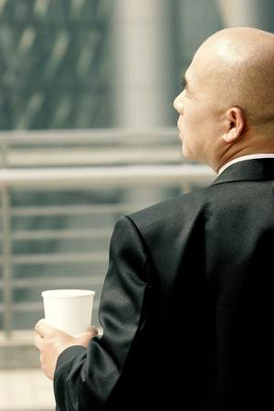 aspirant: Back shot of a bald man in business suit holding a cup