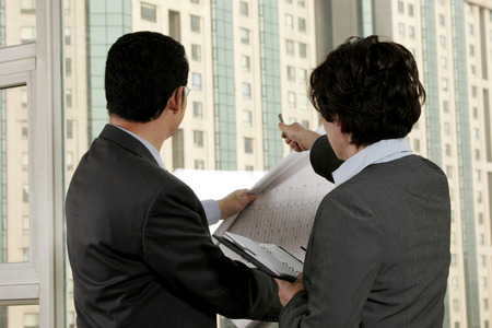Businessman discussing a building plan with his assistant  photo