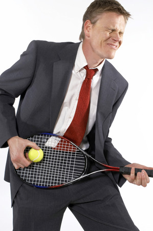 ball like: Businessman holding a tennis racquet and ball like playing a guitar