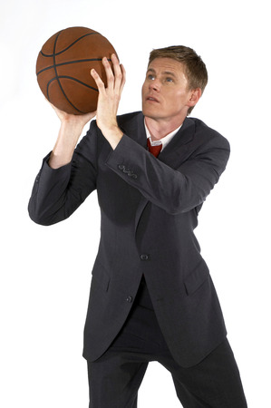 aspirant: Man in business suit trying to shoot a basketball
