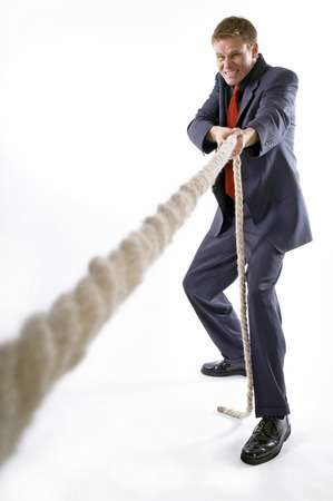 Man in business suit pulling a rope with all his might  photo